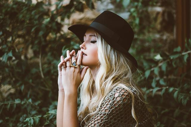 Blondína s čiernym klobúkom a viacerými prsteňmi na rukách.jpg