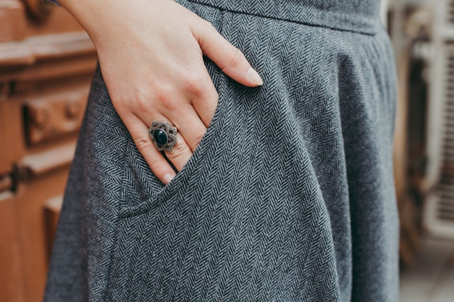 Žena v sivých nohaviciach má na ruke výrazný striebornočierny prsteň.jpg